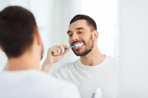 smiling young man brushing teeth and looking at mirror