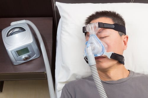 Man with sleep apnea using CPAP machine