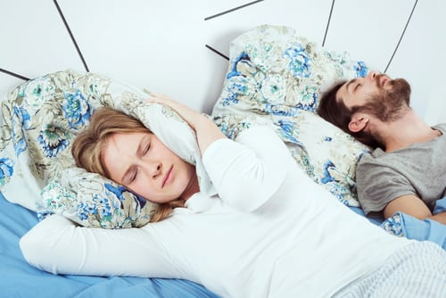 A man and a woman in bed, man is snoring and woman is covering her ears.
