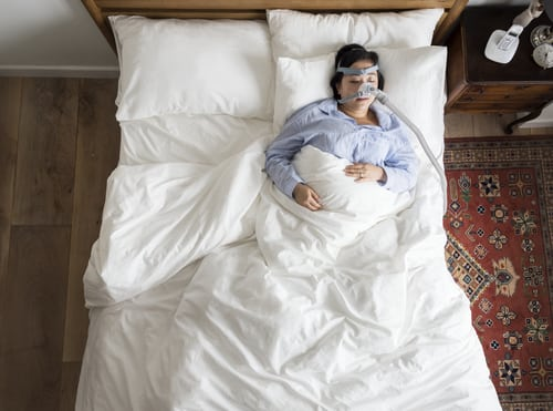 Overhead photo of a woman sleeping with an OSA mask.